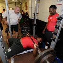 Coach Chuck Dupre keeps a close eye on Reginald DeYoung and Keedrick Simpson as they work out in the weight room at North Caddo.