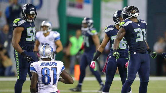 Seahawks strong safety Kam Chancellor (right) celebrates his tackle of Lions wide receiver Calvin Johnson in the second half of Monday's controversial game, which was won 13-10 by Seattle.