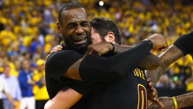 LeBron James hugs Kevin Love after the Cavaliers beat the Warriors on Sunday night.