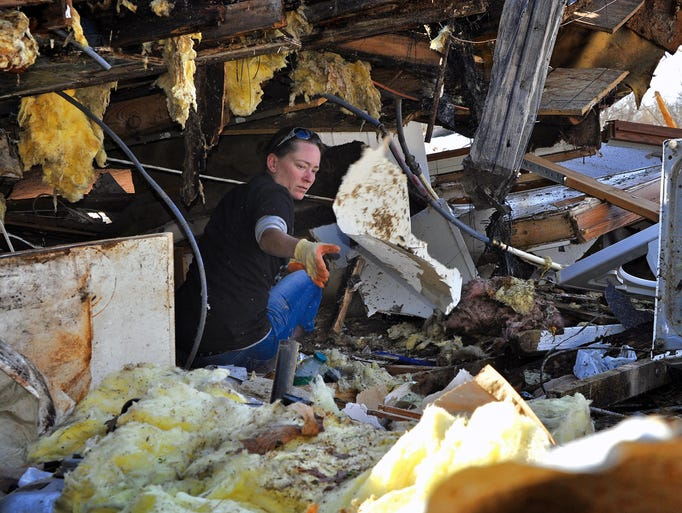 Kris-Tina Dye sorts through the remains of her home in Brookport, Ill. Federal Emergency Management Agency workers on Thursday are expected to begin the initial damage assessments that are required to determine eligibility for federal help.