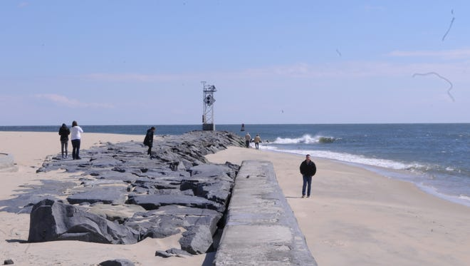 People explore the jetty in Ocean City after a mini sandbar formed due to strong west and southwest winds.