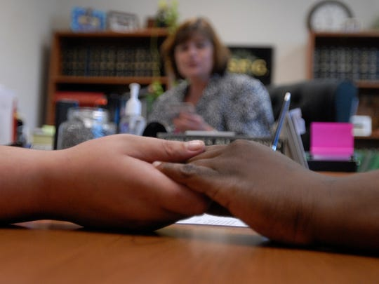 Krystina Lania, left, and India Weatherly hold hands as Northampton Court Clerk Traci Johnson takes personal information before their marriage ceremony Oct. 8 in Eastville. They were the first same-sex couple to get married on the Eastern Shore of Virginia.