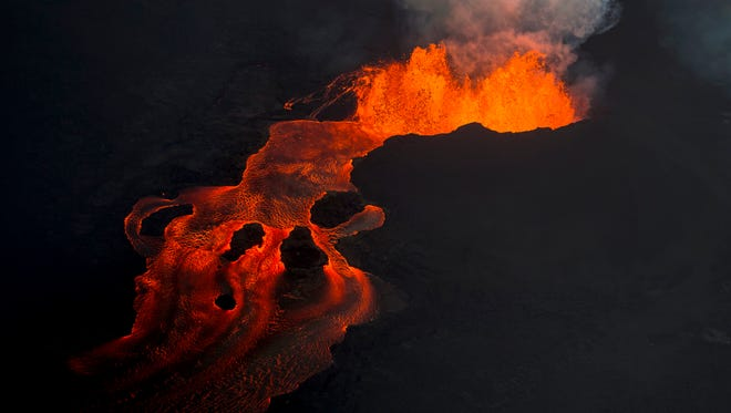 Lava from the Kilauea volcano continues to erupt from a fissure and forms a river of lava flowing down to Kapoho on June 10, 2018, in Pahoa, Hawaii.