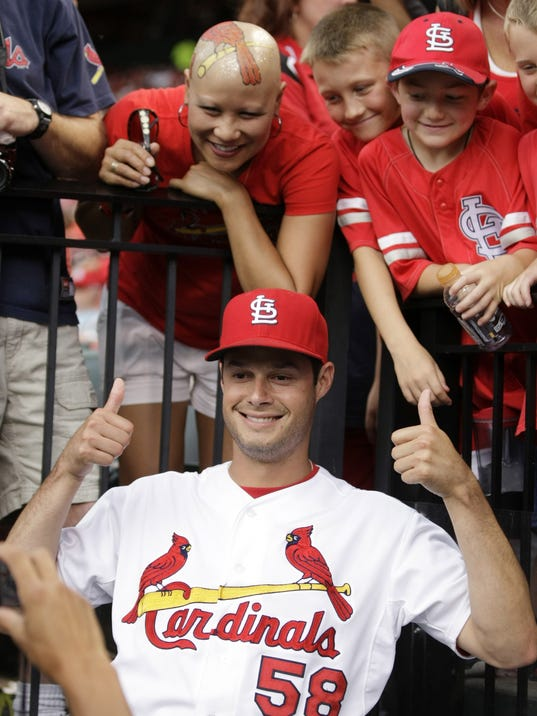 St. Louis Cardinals starting pitcher Joe Kelly poses with fan Moya Brown, upper left, during a rain delay at a baseball game between the Cardinals and the Philadelphia Phillies, Friday, June 20, 2014, in St. Louis. (AP Photo/Tom Gannam)