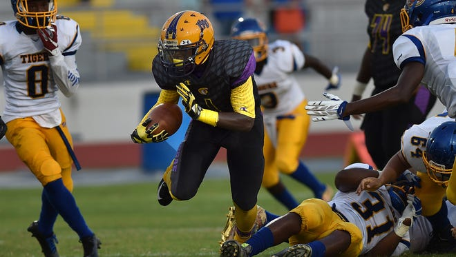 Endravious Knowles (center), of Fort Pierce Central High School, cuts through Clewiston defenders for first down yardage in the first quarter at Lawnwood Stadium in Fort Pierce. (ERIC HASERT/TREASURE COAST NEWSPAPERS)