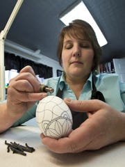 Theresa Somerset uses black-dyed beeswax to outline a design on a goose egg as she creates Ukranian eggs at her home in Essex on Tuesday, April 1, 2014.