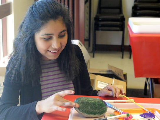 Melinda Beletzuy, 12, decorates her rock with glitter.