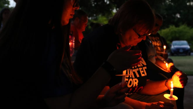 Wichitans bow their heads in prayer Saturday, June 30, 2018, at the Families Belong Together Candlelight Prayer Vigil in Lucy Park. The vigil is part of a nationwide protest to condemn the separating of migrant children from their families at the U.S.- Mexico border.