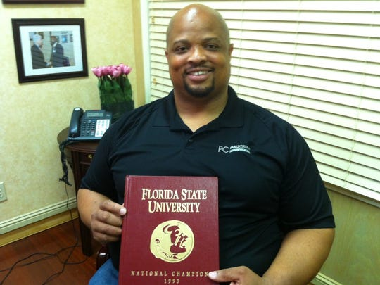 Ken Alexander with a commemorative book that chronicled FSU's 1993 national championship season.