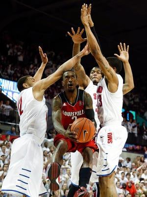 Louisville Cardinals guard Russ Smith drives and scores among three SMU defenders during a game last season.