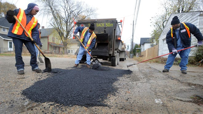 Indianapolis Public Works employees Danica Troutman,left, Torin Harris and Kenneth Stinger Jr., right, work to fill spots of asphalt down in chuckholes in an alley near East Washington Ave and Sherman Drive Thursday morning. (Matt Kryger / The Indianapolis Star)