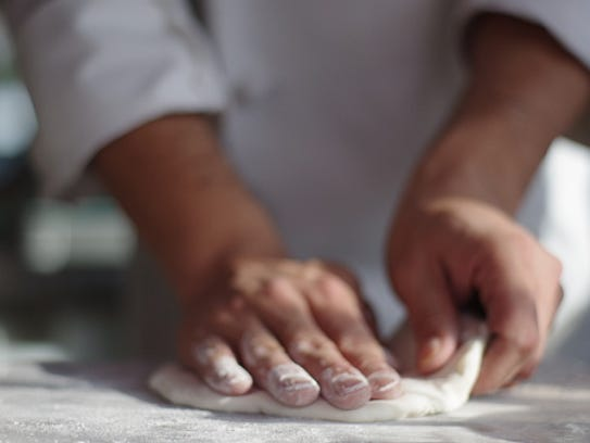 A chef making pizza.