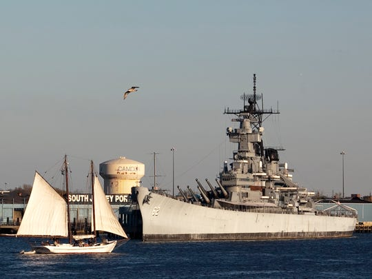 The oyster Schooner A.J. Meerwald, passes by the Battleship New Jersey on a Sunday evening cruise to help benefit the New Jersey museum.
