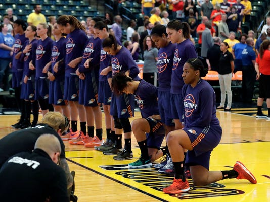"""File-This Sept. 21, 2016, file photo shows, Phoenix Mercury's Kelsey Bone, right, and Mistie Bass, second from right, kneeling during the playing of the national anthem before the start of a first round WNBA playoff basketball game a in Indianapolis.  Bass,  Bone and their Mercury teammates met with Phoenix police a few weeks ago after practice. It was a very eye-opening experience. """"That was such a great opportunity for us to ask some great questions. I don't think the system that is in place in Phoenix is the system in place everywhere,"""" Bass said after practice in New York on Friday as Phoenix prepared for the second round of the playoffs. """"To see a model that is so crystal clear and to talk about their training and how much training they get.""""  (AP Photo/Darron Cummings, File)"""