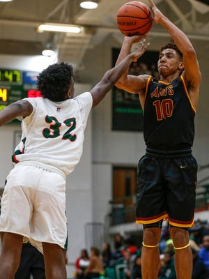 McCutcheon Mavericks guard Robert Phinisee (10) goes up and makes a three point shot against Arsenal Tech Titans forward Windelle Tucker (32) on Thursday, Dec. 28, 2017.