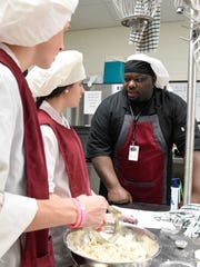 Ernest Hudson, 31, of Dover, works with his culinary arts students Nick Bowen, left and Jamie Calton, middle, both sophmores at Appoquinimick High School to create peach blueberry scones using various ingredients to enhance the recipe.