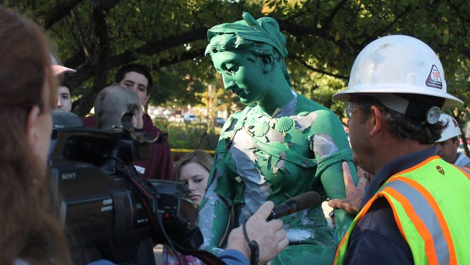 Locals get an close-up look at the beloved Taylor Park fountain topper in St. Albans Wednesday, before its pieces are sent for restoration.