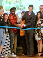 Cincinnati City Councilman P.G. Sittenfeld, center, chair of city council's Education and Entrepreneurship Committee, cuts a ceremonial ribbon to celebrate free Wi-Fi for all of Lower Price Hill.