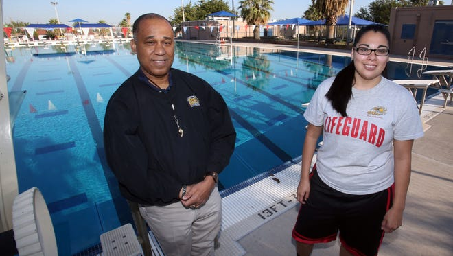 Wayne Thornton, left, marketing and public relations manager for the city Parks and Recreation Department, stands at the Olympic -sized Pavo Real Pool with lifeguard Jessica Hernandez.