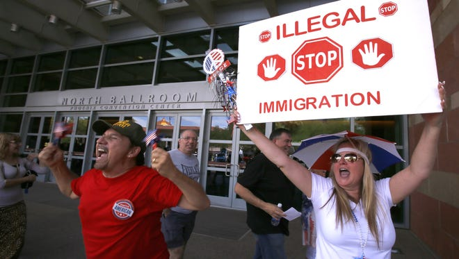 Supporters taunt protesters outside the Phoenix Convention Center where Donald Trump holds a rally Saturday, July 11, 2015 in Phoenix, Ariz.  Donald Trump the business magnate and television personality has risen in polls recently with his unfiltered comments on illegal immigration.