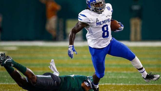 University of Memphis running back Darrell Henderson (right) scrambles past Tulane University defender Donnie Lewis Jr. (left) during first quarter action at Yulman Stadium in New Orleans.