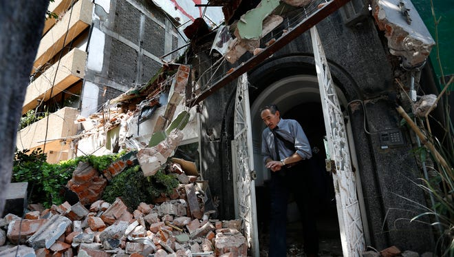 A man walks out of the door frame of a building that collapsed Tuesday after an earthquake in the Condesa neighborhood of Mexico City. Throughout Mexico City, rescue workers and residents dug through the rubble of collapsed buildings in a search for survivors after a deadly 7.1 magnitude quake.