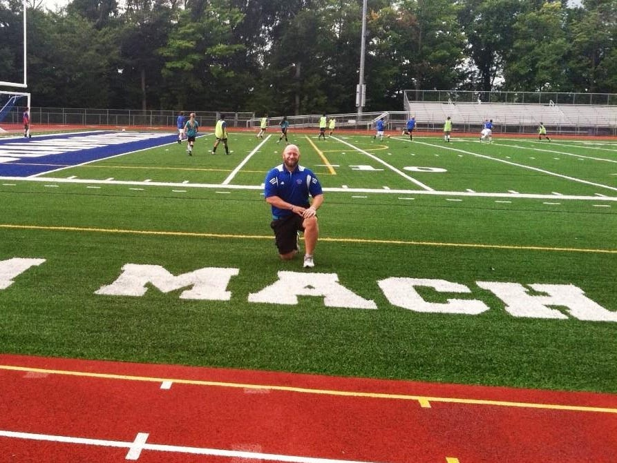 Catholic Central athletic director Aaron Babicz kneels on the new synthetic turf which will be dedicated Aug. 28 in the name of head football coach Tom Mach.