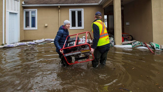 Dominique Paquette, left, and Brad Anderson of Rapid Relief Team, a volunteer organization, carry a pump to her home flooded by waters from the Prairie River on Ile Bizard in western Montreal, Quebec on Wednesday, May 3, 2017.