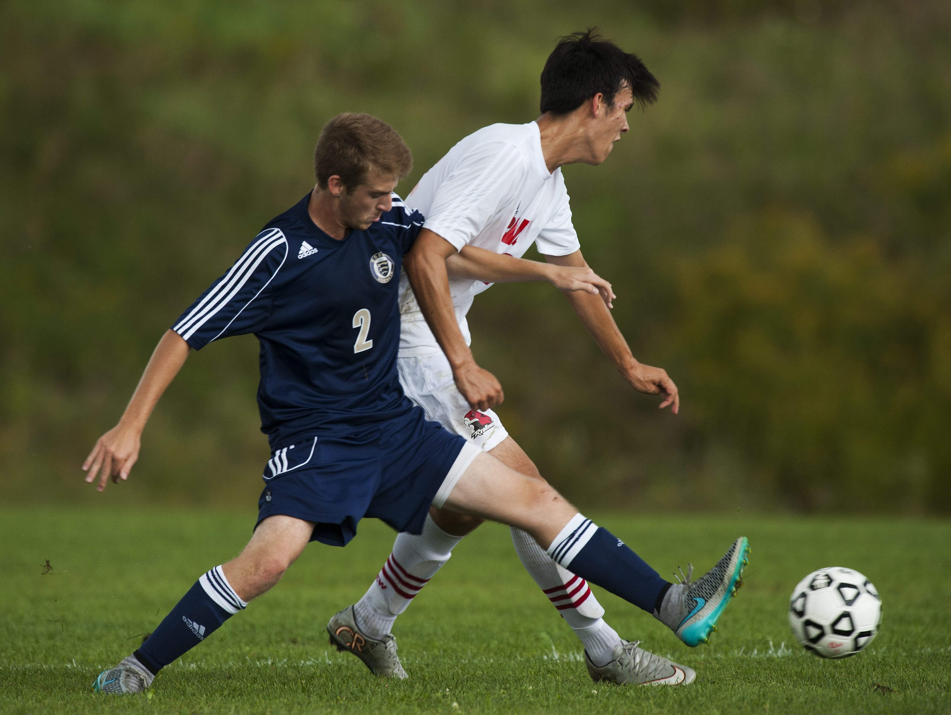 Essex's Aidan Whitney (2) battles for the ball with CVU's Adam Hamilton (22) during the boys varsity soccer game on Wednesday in Hinesburg.