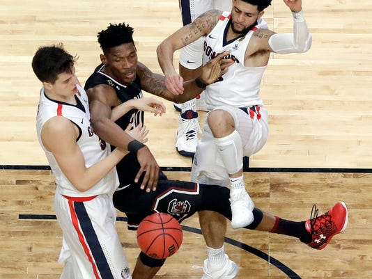 South Carolina's Chris Silva (30) passes the ball between Gonzaga's Zach Collins, left, and Josh Perkins during the second half in the semifinals of the Final Four NCAA college basketball tournament, Saturday, April 1, 2017, in Glendale, Ariz. (AP Photo/David J. Phillip)