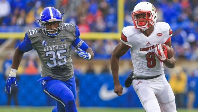 Louisville's Lamar Jackson runs from Kentucky's Denzil Ware in the second quarter Saturday at Commonwealth Stadium.