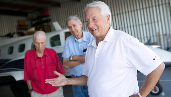 Pilots Jess Bootman (left), Roy Bryan (center), and Bob Stratton (right) stand inside fellow pilot Richard Goldman's hangar at Glendale Municipal Airport on Oct. 5, 2016, in Glendale, Ariz.