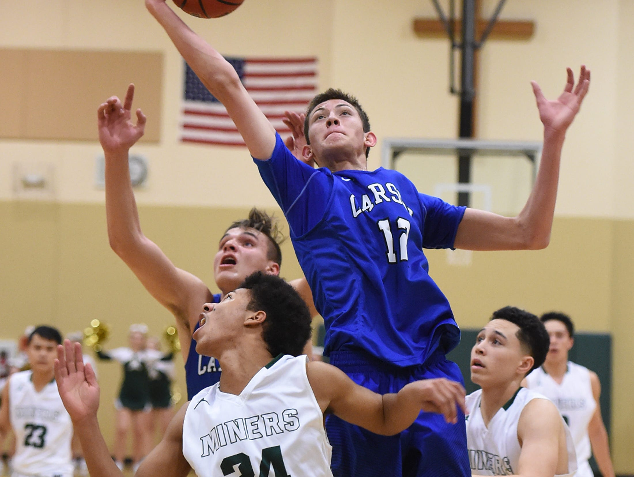 Carson's Trenten Robison reaches to grab a rebound from between Manogue's Josh Rolling, front and Dan Bansuelo, right during the first half of Tuesday's game at Bishop Manogue. Robison's teammate Jayden DeJoseph, behind him, backs him up.