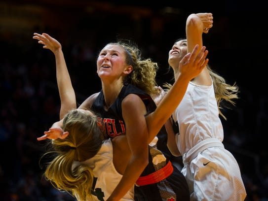 Powell's Haley Schubert (center) takes a shot while