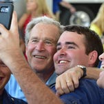 Former President George W. Bush and James Doughty take a selfie during Friday's Hurricane Katrina First Responder Remembrance ceremony in Barksdale Pavilion at Jones Park in Gulfport.