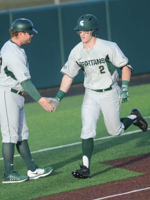 Michigan State's Marty Bechina, right, is congratulated by the Spartans' third base coach after hitting a solo home run in the in the second inning in Game 2 against Abilene Christian on Saturday. He hit two homers in the game in the Spartans' 19-7 victory. They also won the first game 9-7 at Crutcher Scott Field on Saturday.