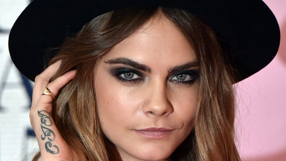 Cara Delevingne shows off her hand tattoo and dark