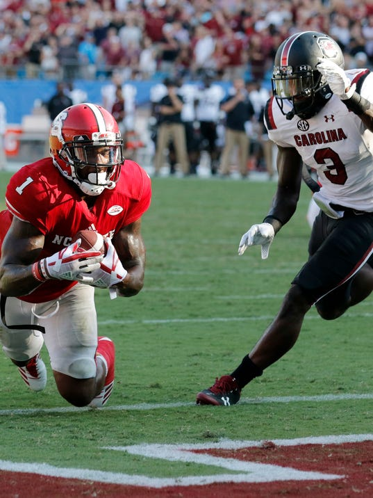 North Carolina State's Jaylen Samuels (1) makes the catch while falling into the end zone as South Carolina's Chris Lammons (3) tries to defend during the second half of an NCAA college football game in Charlotte, N.C., Saturday, Sept. 2, 2017. South Carolina won 35-28. (AP Photo/Bob Leverone)