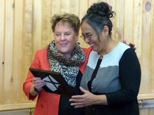 Village manager Debi Lee, left, presents a plaque to Judy Sarabia for her work at the community center and with the RSVP program.