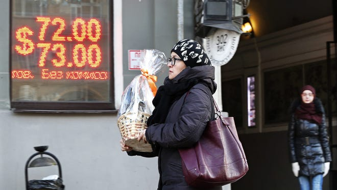 A woman walks past a board listing foreign currency rates against the Russian ruble in central Moscow, Russia Dec. 29, 2015.