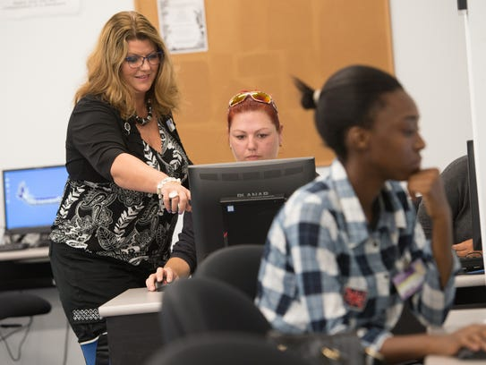 Computer Instructor Lisa Clymer, left, works with nursing