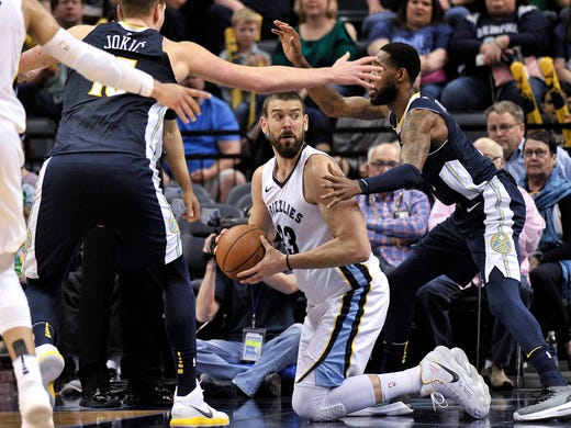 Memphis Grizzlies center Marc Gasol (33) looks to pass the ball from between Denver Nuggets center Nikola Jokic, left, and forward Will Barton during the second half of an NBA basketball game Saturday, March 17, 2018, in Memphis, Tenn. (AP Photo/Brandon Dill)