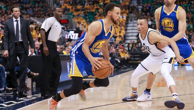 Golden State Warriors guard Stephen Curry controls the ball against Utah Jazz guard Dante Exum during the third quarter in Game 4.