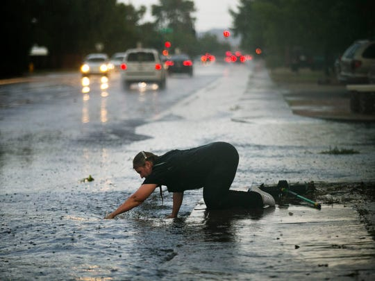 Silvia Graham removes debris from a storm drain in