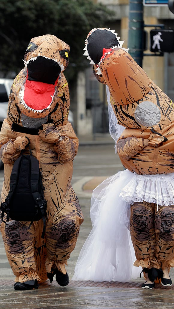 Brian and Tanya Hankinson arrive at the Bexar County Courthouse dressed in dinosaur costumes, Feb. 14, 2018, in San Antonio. The couple took part in a Valentine's Day mass wedding of more than 40 couples at the courthouse.