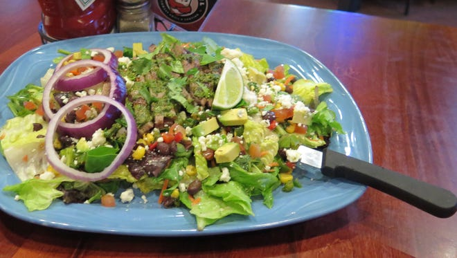 The Chimichurri Steak Salad from Angry Owl Southwest Grill & Cantina features chilled salad greens with tomatoes, fresh avocado, red onions, black bean and corn relish, fresh cilantro and bleu cheese crumbles, all tossed with a cilantro-lime vinaigrette.