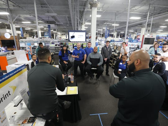 Moblie manager Byron Polanco and Mobile Supervisor Ray Dell Cruz talking with the mobile phone department about what to expect and how to respond to an expected high volume of customers.