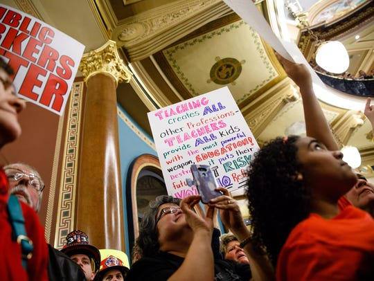 Demonstrators hold signs Monday, Feb. 13, 2017, as