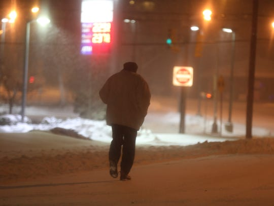 A pedestrian braves the snow and frigid temperatures