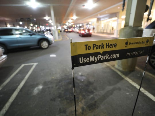 A sign that is placed on each parking location. The sign collapses when the car approaches and the app is activated, and pops back up when the car exits.